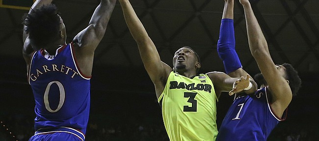 Baylor guard King McClure (3) is fouled by Kansas guard Marcus Garrett (0) as he attempts a shot against Kansas forward Dedric Lawson (1) in the second half of an NCAA college basketball game, Saturday, Jan. 12, 2019, in Waco, Texas. (AP Photo/Jerry Larson)