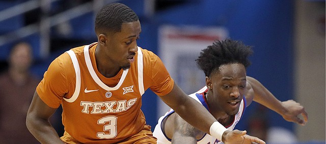 Texas guard Courtney Ramey (3) and Kansas guard Marcus Garrett chase a loose ball during the first half of an NCAA college basketball game Monday, Jan. 14, 2019, in Lawrence, Kan. (AP Photo/Charlie Riedel)
