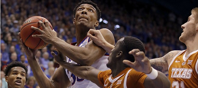 Kansas forward David McCormack shoots under pressure from Texas guard Courtney Ramey (3) and forward Dylan Osetkowski (21) during the first half of an NCAA college basketball game Monday, Jan. 14, 2019, in Lawrence, Kan. (AP Photo/Charlie Riedel)