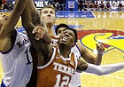 Texas guard Kerwin Roach II (12) and Kansas guard Devon Dotson (11) battle for a rebound during the first half of an NCAA college basketball game Monday, Jan. 14, 2019, in Lawrence, Kan. (AP Photo/Charlie Riedel)