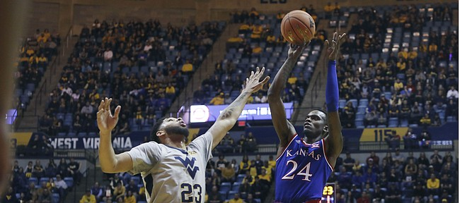 Kansas guard Lagerald Vick (24) shoots over West Virginia forward Esa Ahmad (23) during the first half of an NCAA college basketball game Saturday, Jan. 19, 2019, in Morgantown, W.Va. (AP Photo/Raymond Thompson)