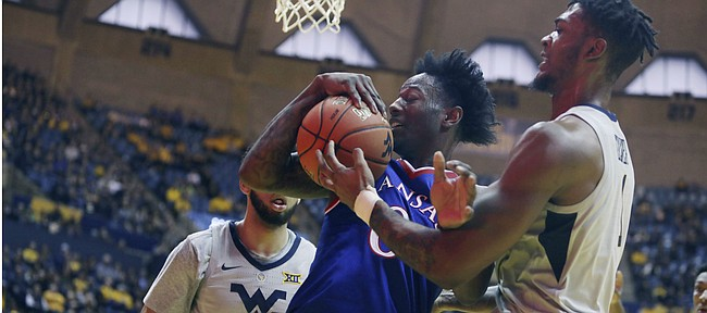 Kansas guard Marcus Garrett (0) grabs a rebound against West Virginia forward Derek Culver (1) during the first half of an NCAA college basketball game Saturday, Jan. 19, 2019, in Morgantown, W.Va. (AP Photo/Raymond Thompson)