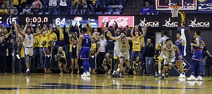 West Virginia players celebrates their 65-64 win over No 7 Kansas in an NCAA college basketball game, Saturday, Jan. 19, 2019, in Morgantown, W.Va.