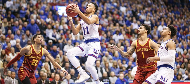 Kansas guard Devon Dotson (11) floats in to the bucket past Iowa State guard Tyrese Haliburton (22) and Iowa State guard Nick Weiler-Babb (1) during the first half, Monday, Jan. 21, 2019 at Allen Fieldhouse. At right is Kansas guard Quentin Grimes (5).