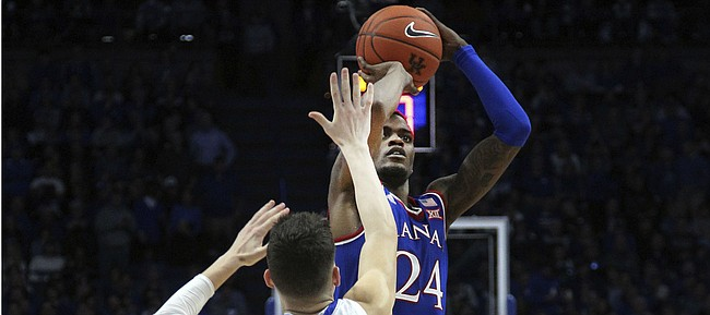 Kansas' Lagerald Vick (24) shoots while defended by Kentucky's Tyler Herro (14) during the second half of an NCAA college basketball game in Lexington, Ky., Saturday, Jan. 26, 2019. Kentucky won 71-63. (AP Photo/James Crisp)