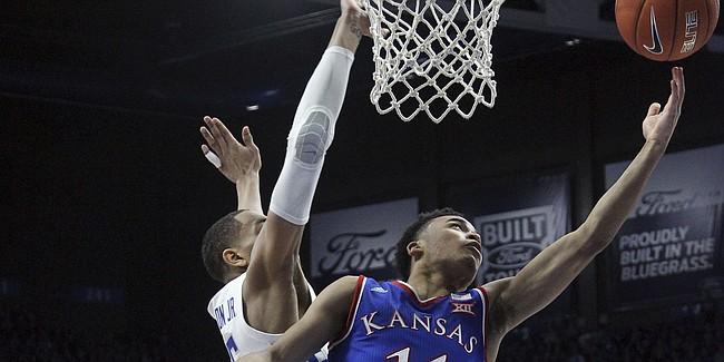 Kansas' Devon Dotson (11) shoots while pressured by Kentucky's PJ Washington during the second half of an NCAA college basketball game in Lexington, Ky., Saturday, Jan. 26, 2019. Kentucky won 71-63. (AP Photo/James Crisp)