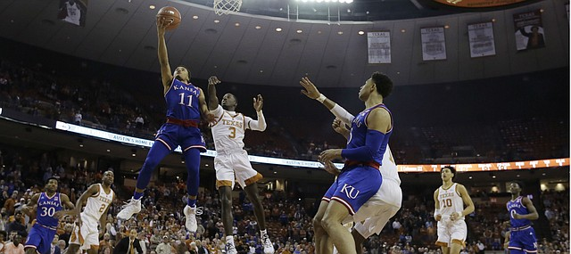 Kansas guard Devon Dotson (11) drives past Texas guard Courtney Ramey (3) to score during the first half on an NCAA college basketball game in Austin, Texas, Tuesday, Jan. 29, 2019. (AP Photo/Eric Gay)