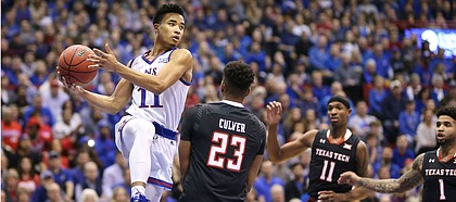 Kansas guard Devon Dotson (11) goes under the bucket as he looks to pass over Texas Tech guard Jarrett Culver (23) during the first half, Saturday, Feb. 2, 2019 at Allen Fieldhouse.