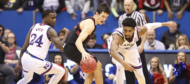 Kansas guard Lagerald Vick (24) and Kansas forward Dedric Lawson (1) look to pressure Stanford guard Cormac Ryan (23) during the second half on Saturday, Dec. 1, 2018 at Allen Fieldhouse.