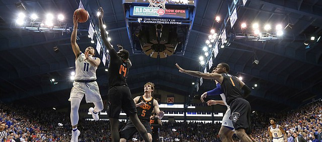 Kansas guard Devon Dotson (11) gets in for a bucket against Oklahoma State forward Yor Anei (14) during the second half, Saturday, Feb. 9, 2019 at Allen Fieldhouse.
