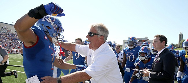 Kansas safety Bryce Torneden (1) gets a hug from defensive analyst Dirk Wedd, who recently retired as long time Lawrence High head coach, after Torneden's interception and touchdown during the first quarter on Saturday, Sept. 15, 2018 at Memorial Stadium.