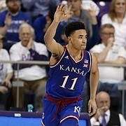 Kansas guard Devon Dotson (11) celebrates sinking a 3-point basket in front of TCU forward Kouat Noi (12) in the second half of an NCAA college basketball game in Fort Worth, Texas, Monday, Feb. 11, 2019.