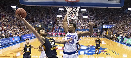 Kansas forward David McCormack (33) soars in to block a shot from West Virginia guard Jermaine Haley (10) during the second half, Saturday, Feb. 16, 2019 at Allen Fieldhouse.