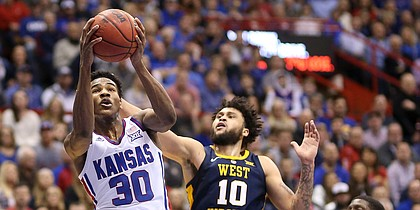 Kansas guard Ochai Agbaji (30) gets in for a bucket past West Virginia guard Jermaine Haley (10) and West Virginia forward Lamont West (15) during the first half, Saturday, Feb. 16, 2019 at Allen Fieldhouse.