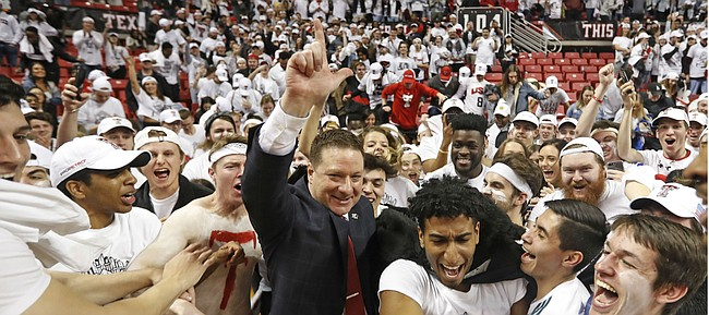 Texas Tech coach Chris Beard is surrounded by fans running onto the court after Texas Tech defeated Kansas 91-62 in an NCAA college basketball game Saturday, Feb. 23, 2019, in Lubbock, Texas. (AP Photo/Brad Tollefson)