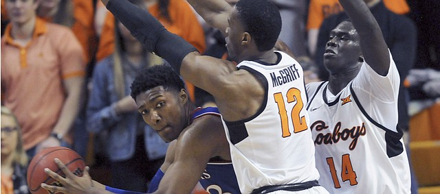 Kansas forward David McCormack, left, looks for an open teammate while under pressure from Oklahoma State forwards Cameron McGriff, center, and Yor Anei during an NCAA college basketball game in Stillwater, Okla., Saturday, March 3, 2019. (AP Photo/Brody Schmidt)