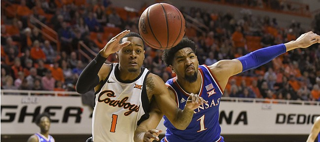 Oklahoma State forward Curtis Jones, left, and KU's Dedric Lawson struggle for a loose ball during an NCAA college basketball game in Stillwater, Okla., Saturday, March 3, 2019. (AP Photo/Brody Schmidt)