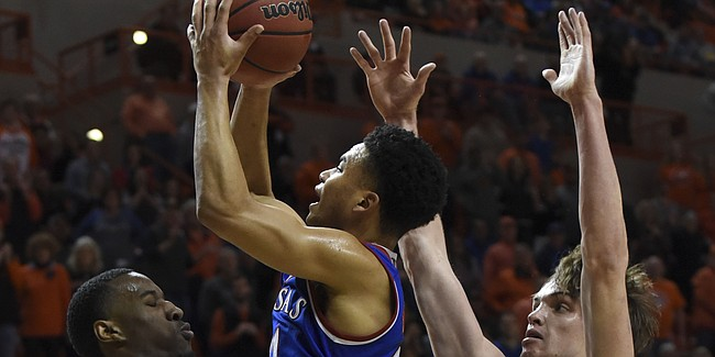 Oklahoma State forward Cameron McGriff, left, takes a charge from Kansas guard Devon Dotson, center, while being pressured by Oklahoma State forward Duncan Demuth during an NCAA college basketball game in Stillwater, Okla., Saturday, March 3, 2019. Kansas defeated Oklahoma State 72-67. (AP Photo/Brody Schmidt)