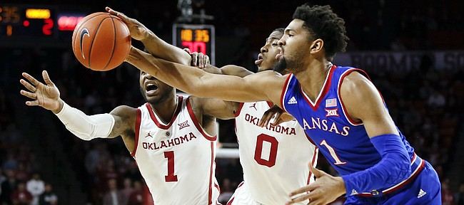 From left, Oklahoma guard Rashard Odomes (1), Oklahoma guard Christian James (0) and Kansas forward Dedric Lawson (1) chase a loose ball in the first half of an NCAA college basketball game in Norman, Okla., Tuesday, March 5, 2019. (AP Photo/Nate Billings)