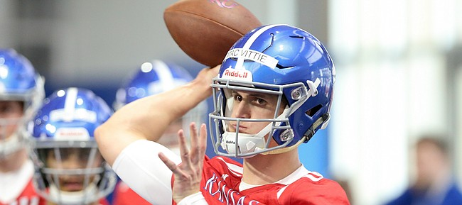 Kansas quarterback Thomas MacVittie pulls back to throw during football practice on Wednesday, March 6, 2019 within the new indoor practice facility.