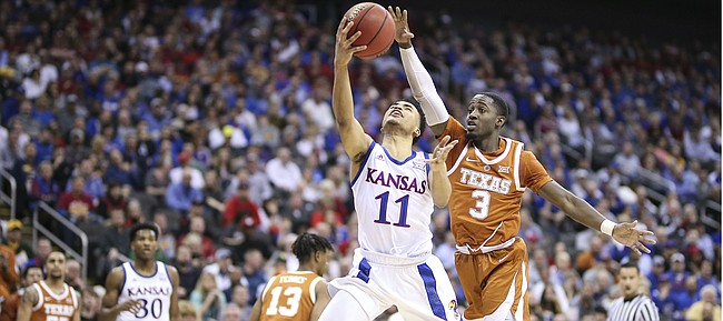 Kansas guard Devon Dotson (11) gets in to put up a shot past Texas guard Courtney Ramey (3) during the first half, Thursday, March 14, 2019 at Sprint Center in Kansas City, Mo.