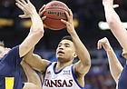 Kansas guard Devon Dotson (11) cuts between West Virginia guard Jordan McCabe (5), left, and West Virginia forward Logan Routt (31) during the first half in Kansas City, Mo.