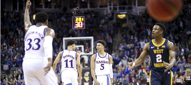 Kansas guard Quentin Grimes (5) celebrates with Kansas guard Devon Dotson (11) after connecting on a three pointer during the first half, Friday, March 15, 2019 at Sprint Center in Kansas City, Mo.