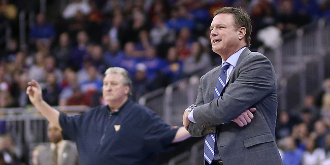 Kansas head coach Bill Self and West Virginia head coach Bog Huggins, background, watch from the sidelines during the second half, Friday, March 15, 2019 at Sprint Center in Kansas City, Mo.