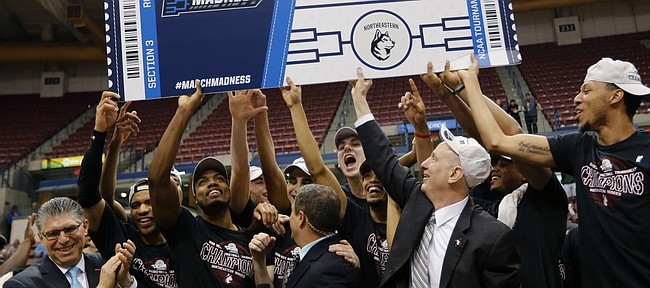 Northeastern head coach Bill Coen, second from right in front, celebrates with his team after defeating Hofstra 82-74, in an NCAA college basketball game to win the Colonial Athletic Association men's basketball championship, Tuesday, March 12, 2019, in North Charleston, S.C. (AP Photo/Mic Smith)