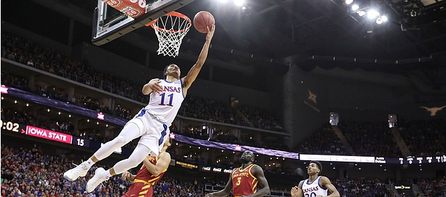 Kansas guard Devon Dotson (11) lunges under the bucket for a shot during the first half, Saturday, March 16, 2019 at Sprint Center in Kansas City, Mo.