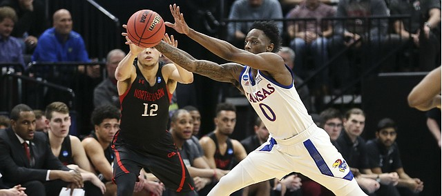 Kansas guard Marcus Garrett (0) steps in front of a pass to Northeastern guard Jordan Roland (12) for a steal during the second half, Thursday, March 21, 2019 at Vivint Smart Homes Arena in Salt Lake City, Utah.