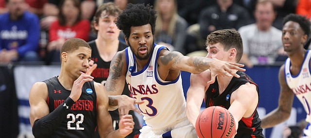 Kansas guard K.J. Lawson (13) looks to disrupt a pass between Northeastern guard Donnell Gresham Jr. (22) and Northeastern forward Tomas Murphy (33) during the first half, Thursday, March 21, 2019 at Vivint Smart Homes Arena in Salt Lake City, Utah.
