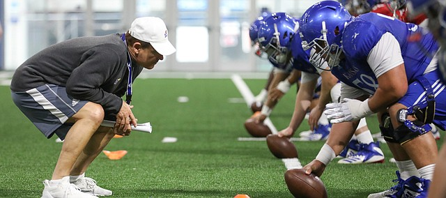 Kansas head coach Les Miles gets down as he works with the offensive line on Thursday, April 4, 2019 at the indoor practice facility.