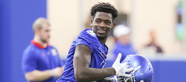 Kansas receiver Daylon Charlot smiles as he puts on his helmet while running to a drills station during football practice on Wednesday, March 6, 2019 within the new indoor practice facility.