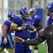 Kansas head coach Les Miles works with offensive lineman Api Mane on Thursday, April 4, 2019 at the indoor practice facility.