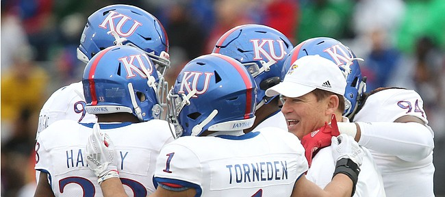 Kansas head coach Les Miles hops in the huddle with Bryce Torneden and the defense during Late Night Under the Lights on Saturday, April, 13, 2019 at Memorial Stadium.