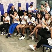 Members of the Kansas tennis team react to seeing that they will host NCAA Tournament matches beginning on Friday at Rock Chalk Park.