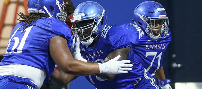 Kansas offensive lineman Hakeem Adeniji works against fellow lineman Malik Clark (61) on Thursday, April 4, 2019 at the indoor practice facility.