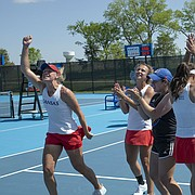 The Kansas tennis team celebrates a a 4-2 win against Florida Saturday at the Jayhawk Tennis Center. Kansas advances to the Sweet 16 next weekend.