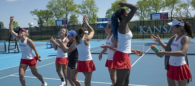 The Kansas tennis team celebrates a a 4-2 win against Florida Saturday at the Jayhawk Tennis Center. Kansas advances to the Sweet 16 next weekend.