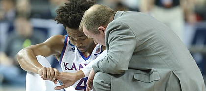 Kansas guard Devonte' Graham (4) sits on the floor with trainer Bill Cowgill after suffering an injury during the first half, Saturday, March 17, 2018 in Wichita, Kan.