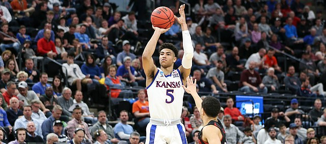 Kansas guard Quentin Grimes (5) puts up a three over Northeastern guard Jordan Roland (12) during the second half, Thursday, March 21, 2019 at Vivint Smart Homes Arena in Salt Lake City, Utah.
