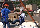 "Kansas football coach Les Miles begins rappelling down from the roof of 888 Lofts in downtown Lawrence on Saturday, June 1. Miles was one of many participants at the ""Over The Edge"" event, which raised money for the Boys & Girls Club of Lawrence."