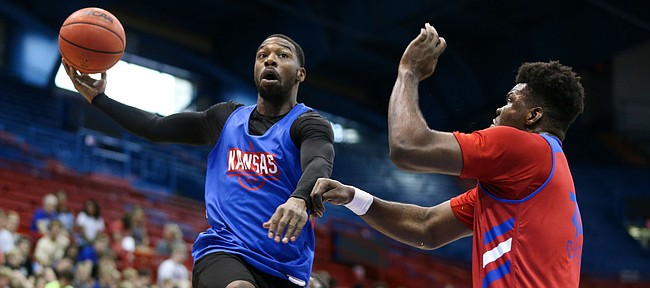 Former Kansas guard Elijah Johnson tosses an over-the-shoulder pass while defended by Kansas center Udoka Azubuike during a scrimmage on Tuesday, June 11, 2019 at Allen Fieldhouse.