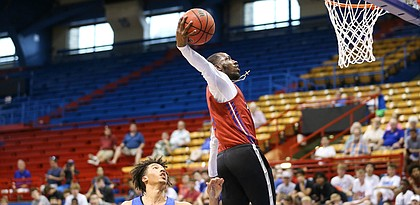 Former Kansas guard Tyshawn Taylor pulls back to dunk off a breakaway past Kansas forward Jalen Wilson during a scrimmage on Tuesday, June 18, 2019 at Allen Fieldhouse.