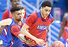 Kansas freshman Tristan Enaruna pushes the ball up the court as fellow freshman Isaac McBride defends during a scrimmage on Tuesday, June 11, 2019 at Allen Fieldhouse.