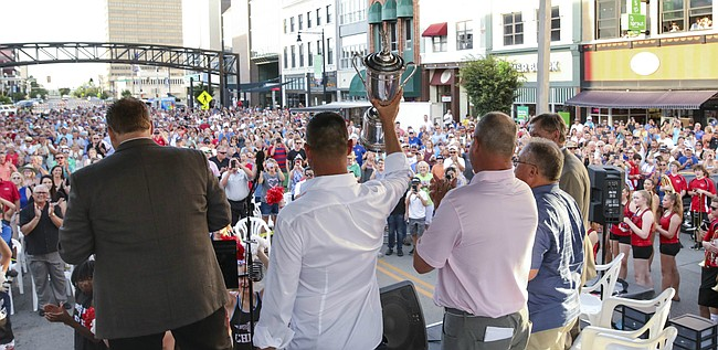 Golfer Gary Woodland hoists the U.S. Open Championship trophy as he takes the stage during a block party along Kansas Ave. in Topeka on Tuesday, July 2, 2019. Woodland, who recently won the U.S. Open at Pebble Beach, was celebrated in his home town.