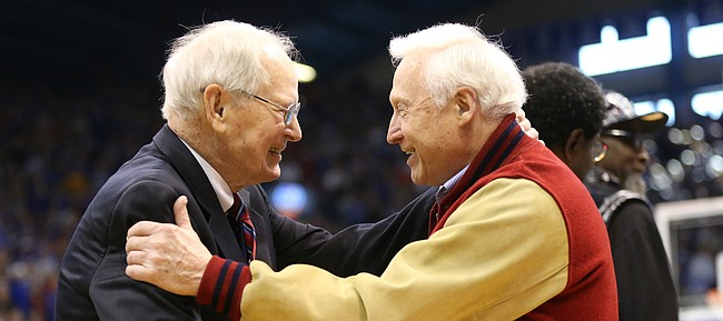Ted Owens, left, is greeted by a former Kansas player during a halftime ceremony in recognition of 120 years of Kansas basketball.