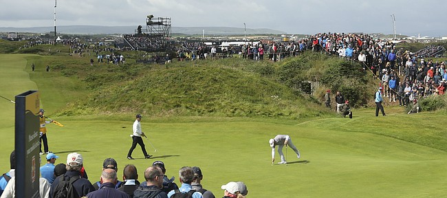 Gary Woodland of the United States picks his ball out of the 4th green during the first round of the British Open Golf Championships at Royal Portrush in Northern Ireland, Thursday, July 18, 2019.