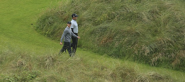 Northern Ireland's Rory McIlroy, left looks up as he walks from the 7th tee with Gary Woodland of the United States during the second round of the British Open Golf Championships at Royal Portrush in Northern Ireland, Friday, July 19, 2019.